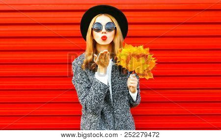 Stylish Funny Autumn Woman Sends An Air Kiss With Yellow Maple Leaves, Wearing A Coat On Red Backgro