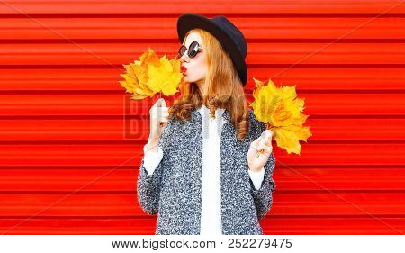 Pretty  Stylish Autumn Pretty Woman With Yellow Maple Leaves, Wearing A Coat On Red Background
