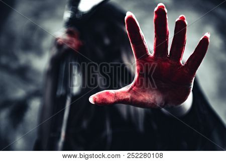 Witch Showing Bloody Hand With Reaper. Female Demon Angel In Black Clothes And Hood On Grunge Wall B