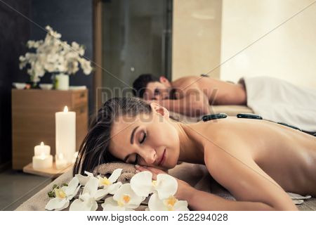 Young couple relaxing under the stimulating effects of a traditional hot stone massage at luxury spa and wellness center