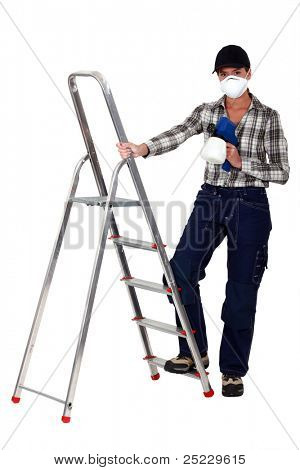 Tradesperson holding a spray gun and standing next to a stepladder