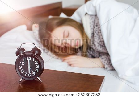 Young Woman Sleep With Alarm Clock Near The Bed In The Morning. Sleeping Girl And Alarmclock In Bedr