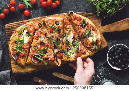 Flatbread Pizza Garnished With Fresh Arugula On Wooden Pizza Board, Top View. Dark Stone Background.