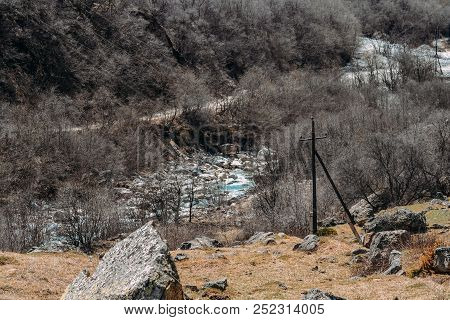 Stone Terrain And Dry Trees As Well As A River In The Daytime