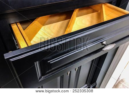 Black kitchen cabinets. Modern base cabinets with chrome cabinet handles. Modern Cabinets. Contemporary Italian kitchen cabinet design. Base doors and drawers of wooden kitchen cabinet.