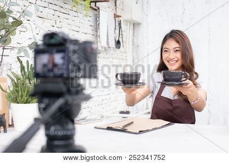 Asian Barista Looking To Camera For Live To Social Media. Female Barista Using Social Media To Promo