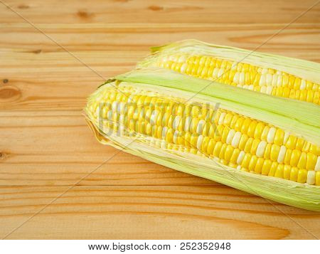 Ears of bicolor sweet corn on rustic wooden background poster
