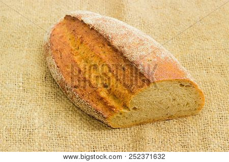 Partly cut wheat and rye sprouted bread with added whole sprouted wheat grains, rye malt and molasses lying on a sackcloth with selective focus poster