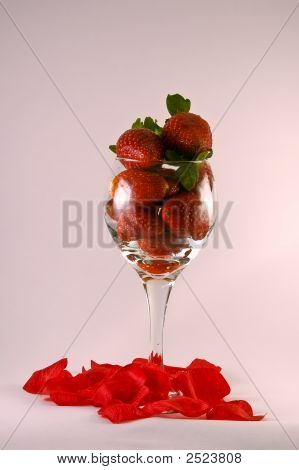 Wine Glass Filled With Strawberries And Rose Pedals