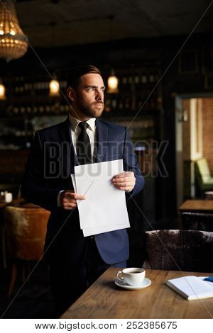 Serious ambitious handsome male entrepreneur in formal suit holding papers and looking aside while thinking of plans and standing at table in restaurant