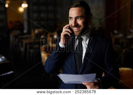 Cheerful excited handsome event manager in suit checking lists and planning banquet in restaurant, he laughing and talking on mobile phone