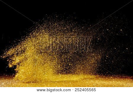 Real gold glitter particles  isolated on black background