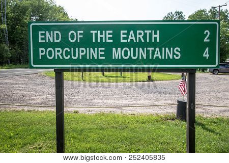 Funny Highway Road Signs. Mileage Marker For The Porcupine Mountains Wilderness State Park In The Up