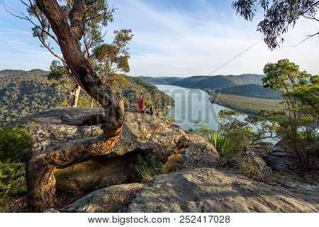 Female Sitting On A Large Rock Relaxing In Afternoon Dappled Light The Australian Bushland With View