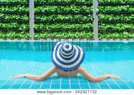 Young Asian Woman Relaxing In Swimming Pool At Spa Resort. Relaxing Concept. Beautiful Young Woman I