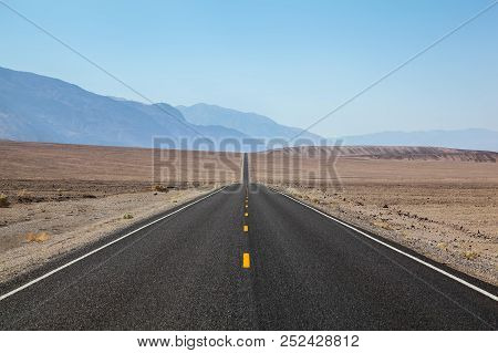 Endless And Lonely Blacktop Road Disappearing Into The Horizon Near Death Valley National Park