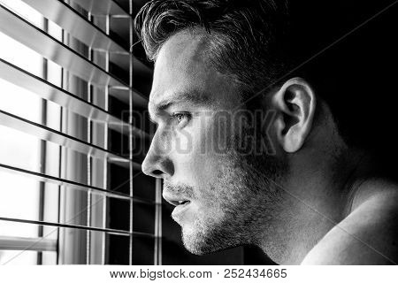 Hunky male shirtless man with pecs and muscles looking out of window with wood blinds.