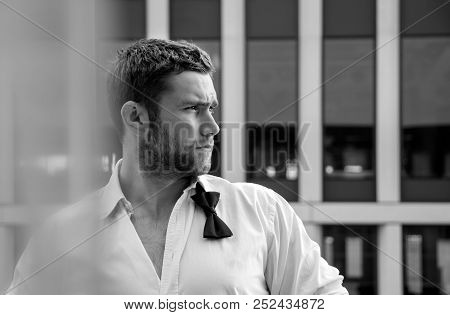 Handsome Hunky Man With Unbuttoned Shirt And Loose Bowtie Stands On Hotel Balcony With Sckyscraper B