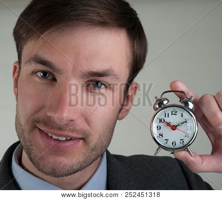 Businessman Is Holding An Alarm Clock. Age Of Forty Years.