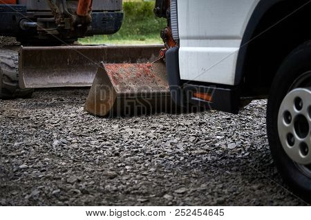 Digger And Truck At Concrete Yard At Construction Site