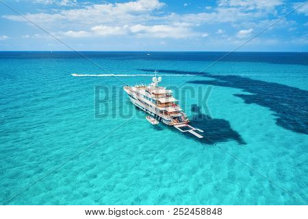 Yacht On The Azure Seashore In Balearic Islands. Aerial View Of Floating Boat With People In Transpa
