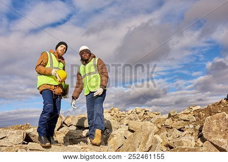 Full Length Portrait Of Two Industrial Workers Wearing Reflective Jackets, One Of Them African, Stan