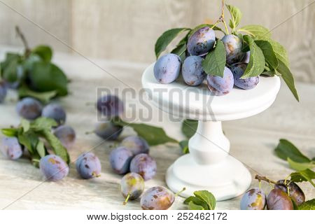 Many Juicy Beautiful Amazing Nice Plums On Light Wooden Background.