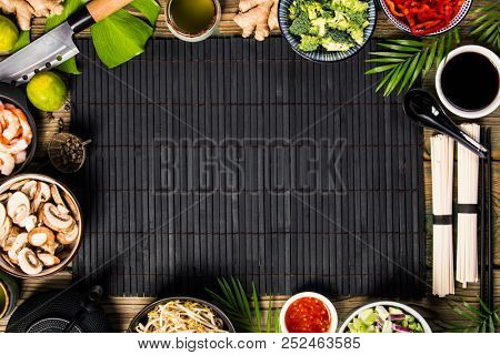 Asian cuisine ingredients on bamboo mat over old wooden background, top view. Vegetables, spices, shrimp, noodles, sauces for cooking vietnamese, thai or chinese food. Clean eating food concept