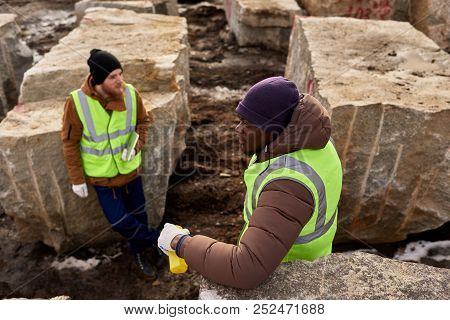 High Angle View Of Two Industrial Workers Wearing Reflective Jackets Resting Standing Against  Grani