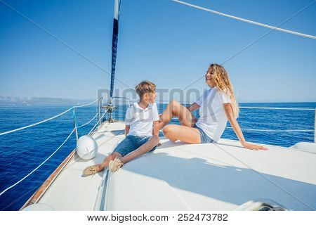 Boy With His Sister On Board Of Sailing Yacht On Summer Cruise. Travel Adventure, Yachting With Chil