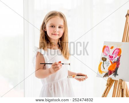 Portrait of a beautiful little girl drawing on easel. Creative child girl making a picture