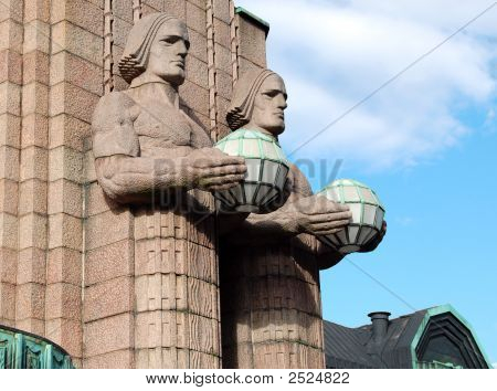 Two Statues Of Men With Lamps