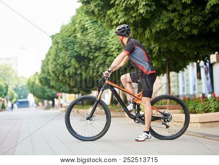 Side View Of Guy Cyclist In Cycling Clothes And Helmet Looking Away Getting Ready To Cross City Stre