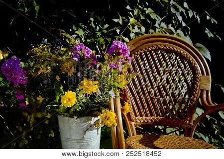 Wicker Chair And A Floor Vase With Flowers In An Autumn Garden, Outdoor Contrast Shot