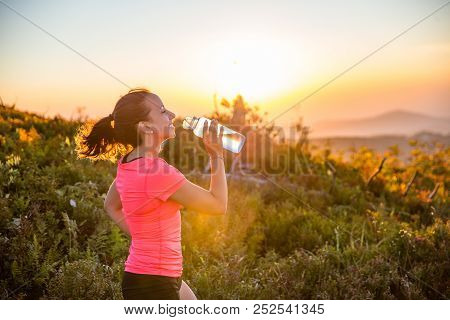 Thirsty Woman Trail Runner Drinking Water From Water Bottle.