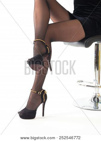 Sexy Woman Wearing High Heels Shoes And Short Skirt Sitting In Office Chair. Isolated On White