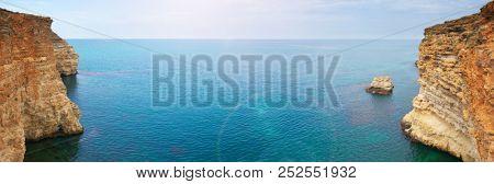 Mountain sea bay rocks panoramic landscape. Sea bay rocks view in mountains. Seascape nature composition. Mountain sea bay rock cliff view.