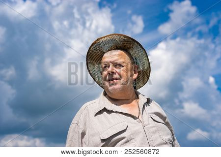 Nice Portrait Of Ukrainian Senior Farmer In Straw Hat Against Blue Cloudy Sky