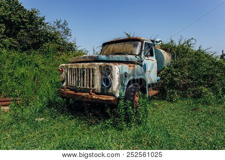 Old Rusty Overgrown Truck. Abandoned Soviet Tank Car In Ghost Town.