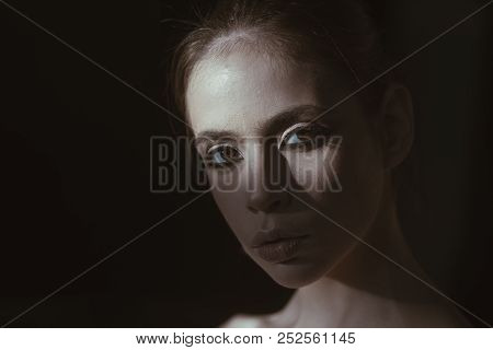 Face Of Pretty Woman With Make Up In Darkness. Mysterious Girl Hiding From Day Light. Portrait Calm