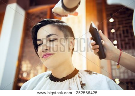 Beauty, hairstyle, treatment, hair care concept, young woman and hairdresser cutting hair at hairdressing salon. Hairdresser cuts girl's hair. Hairstylist serving client at barber shop