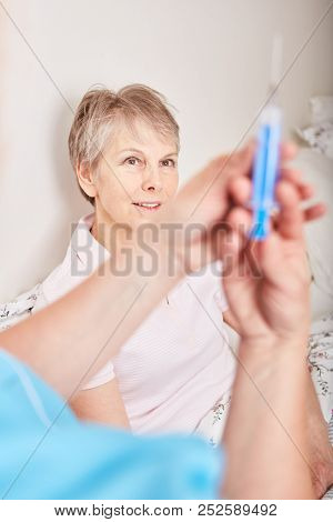 Nurse holds syringe while senior woman as patient observes