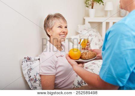 Nurse serves senior woman healthy breakfast in bed