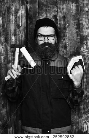 Holding Various Building Tools: Saw, Hammer, Roller Paint With Serious Face On Brown Wooden Studio B