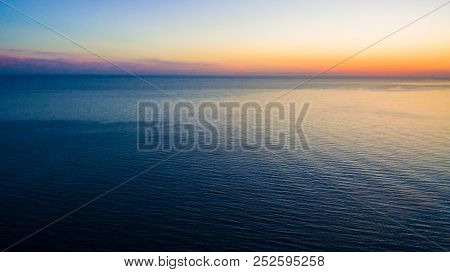 Drone View Of A Wide Sea Surface And The Horizon At Sunset