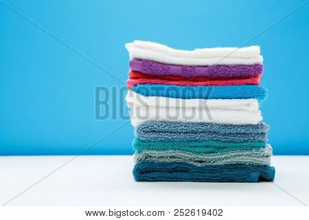 Photo of multi-colored bath towels on empty blue background.