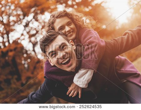 Happy Young Couple On Autumn. Bottom View. Beautiful White Woman. Handsome Man In Park. Outdoor. Lov