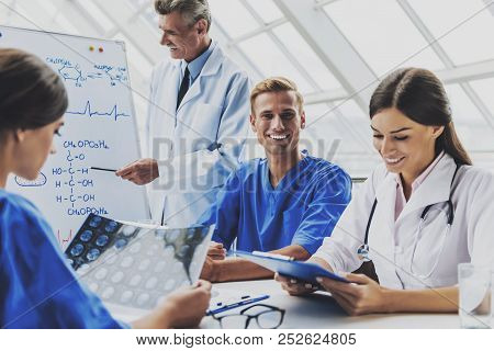 Attractive Happy Doctors. Smiling At Meeting. Doctor With Crossed Hands. Clinic On Background. Famal