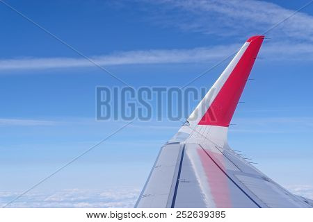 Airplane Wing With Red Colored Winglet Against Blue Sky. View From Porthole