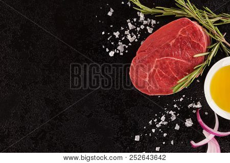 Raw Beef Steak With Rosemary, Salt And Olive Oil On Black Background With Copy Space. Culinary Eatin